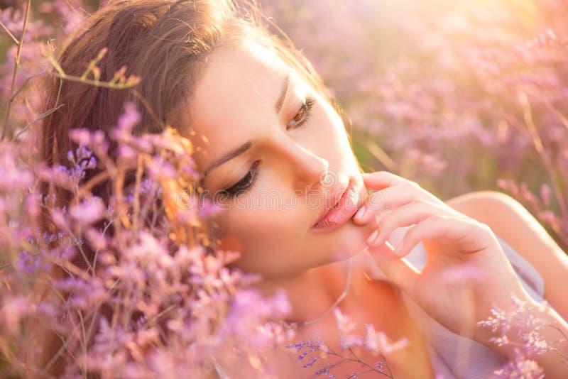 Flicka som ligger på en äng arkivfoton