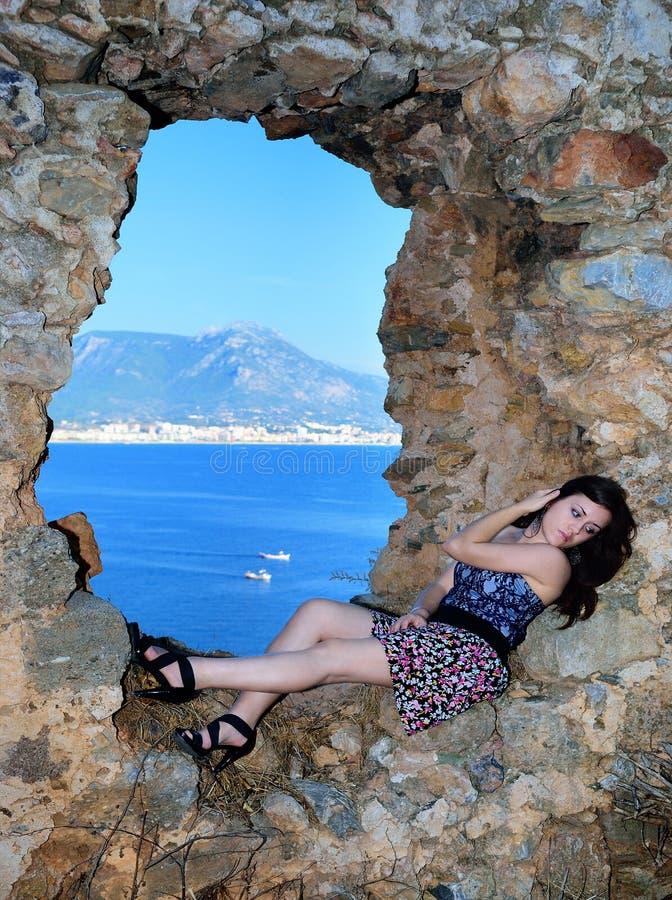 Flicka som ligger på en stenvägg nära havet royaltyfri fotografi
