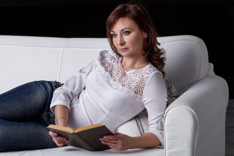 Flicka som ligger på en vit soffa arkivbild
