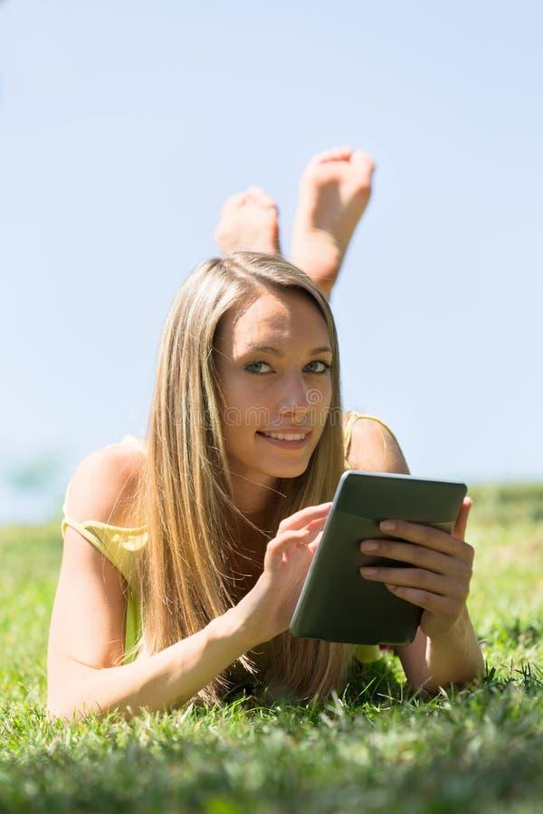 Flicka som ligger på gräs i ängen som tycker om läs- ereader royaltyfri foto