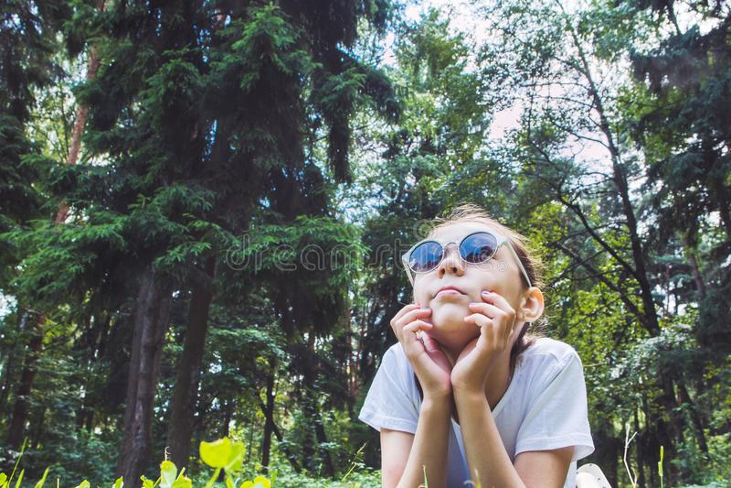 Flicka som ligger på gräset och ser upp, tonad bild royaltyfri bild