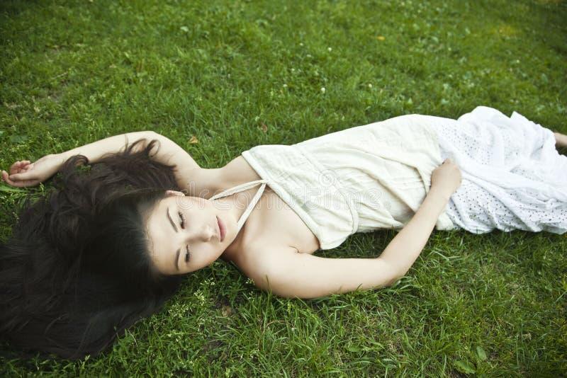 Flicka som ligger på grönt gräs royaltyfri foto