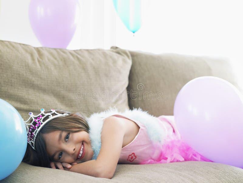 Flicka som ligger på Sofa With Balloons arkivfoton