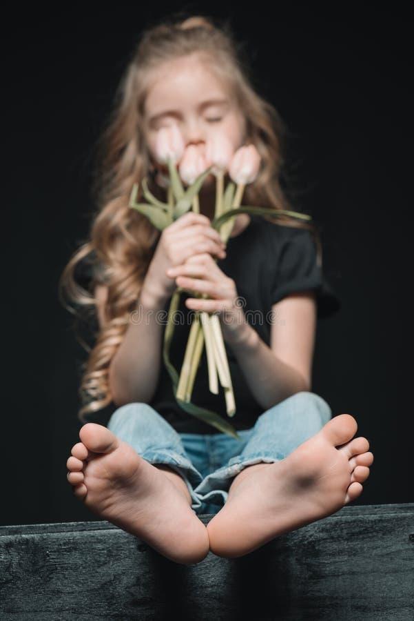 Flicka som luktar tulpanbuketten på svart arkivfoto