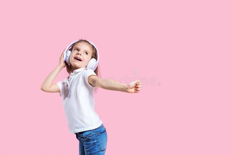 Flicka som lyssnar till musik i h?rlurar p? rosa bakgrund Gulligt barn som tycker om lycklig dansmusik, det n?ra ?gat och leende arkivfoton
