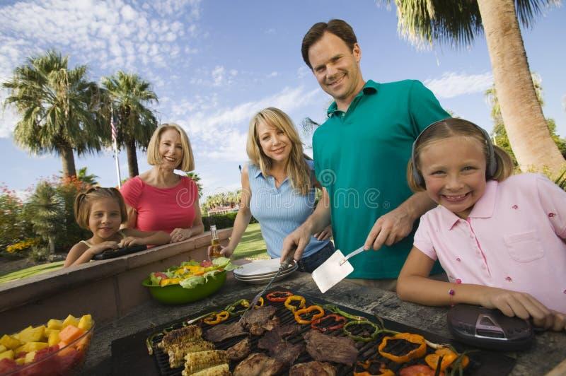 Flicka (7-9) som lyssnar till spelaren för bärbar musik på den utomhus- grillfesten med föräldrar för syster (7-9) och farmorståen arkivfoton