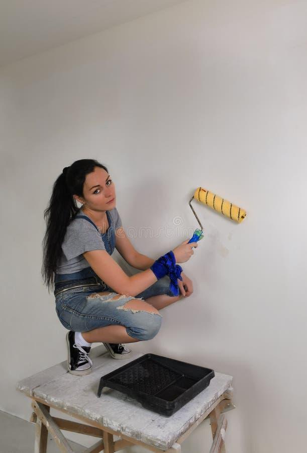 Flicka som målar en vägg i hennes hus royaltyfri fotografi