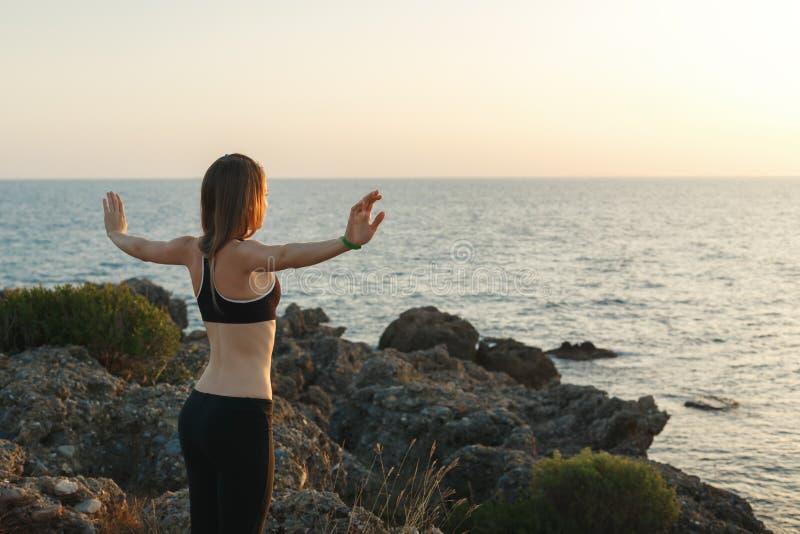 Flicka som mediterar på stranden på solnedgången arkivbild