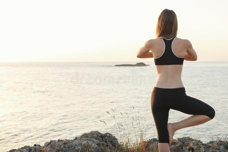 Flicka som mediterar på stranden på solnedgången royaltyfri foto