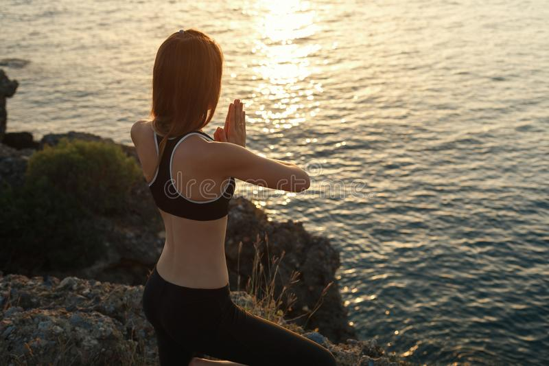 Flicka som mediterar på stranden på solnedgången royaltyfria foton