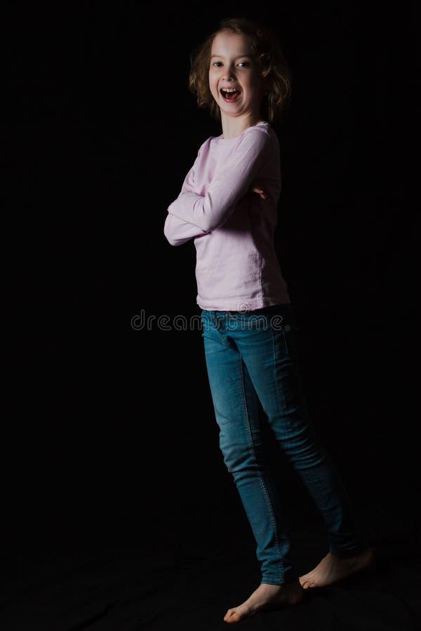 Flicka som naturligt ler och poserar på svart bakgrund fotografering för bildbyråer