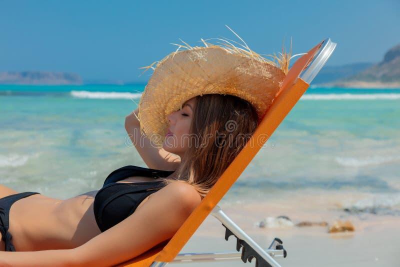 Flicka som ner ligger på dagdrivare på den Balos stranden royaltyfria bilder