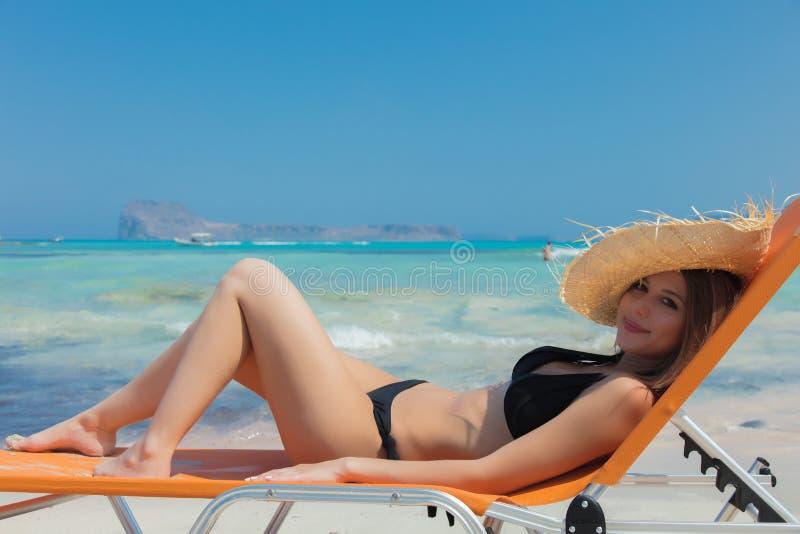 Flicka som ner ligger på dagdrivare på den Balos stranden royaltyfri foto