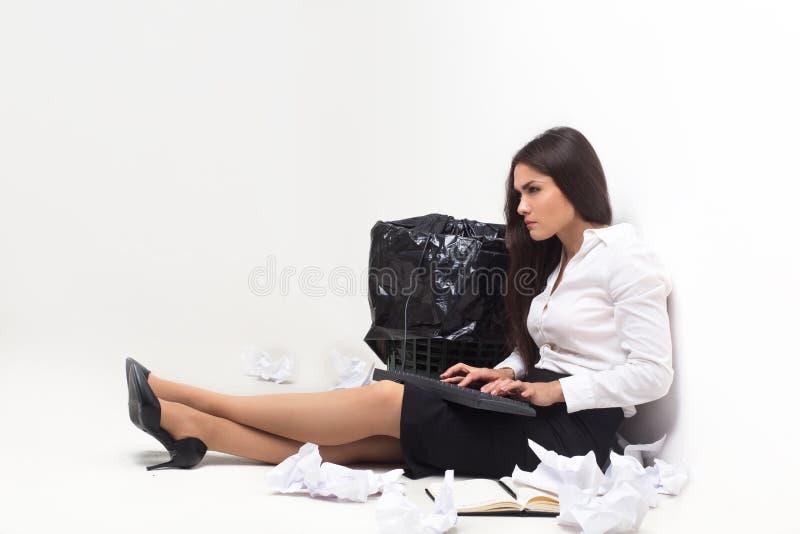 Flicka som ner sitter bredvid avfallfack arkivfoto