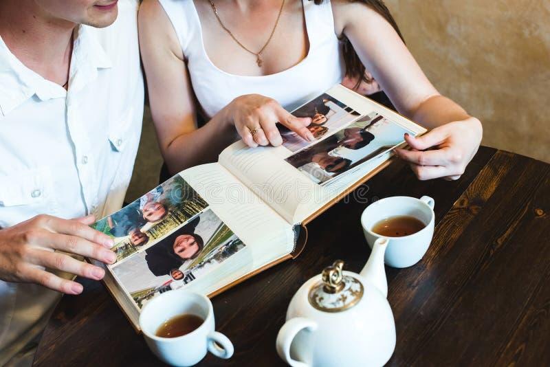 Flicka som pekar på fotoet i albumet arkivbilder