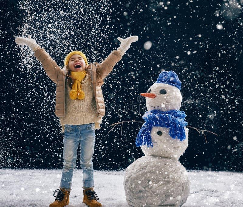 Flicka som plaing med en snögubbe royaltyfri foto