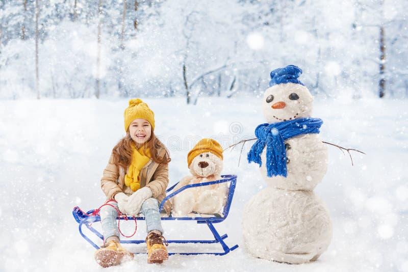 Flicka som plaing med en snögubbe arkivbild