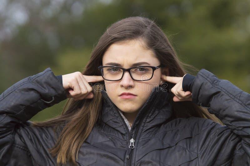 Flicka som pluggar henne öron royaltyfri foto