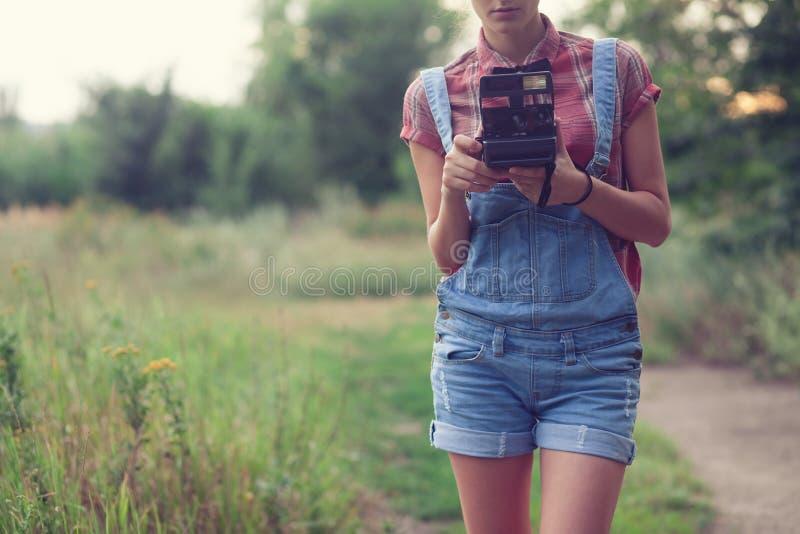 Flicka som poserar med den ögonblickliga kameran arkivfoton