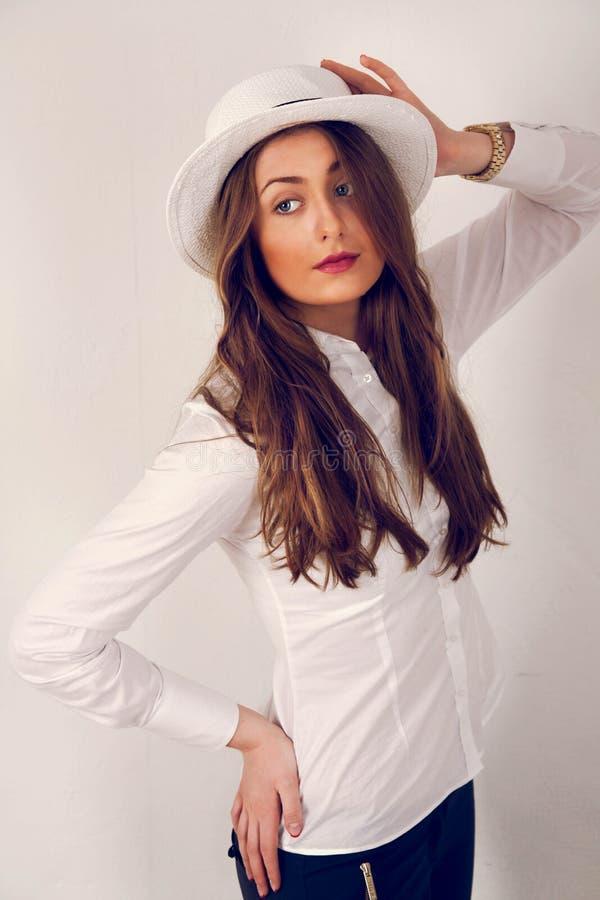 Flicka som poserar med en hatt fotografering för bildbyråer