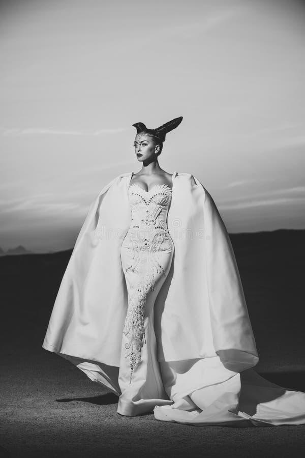 Flicka som poserar på ökensolnedgånghimmel royaltyfri fotografi