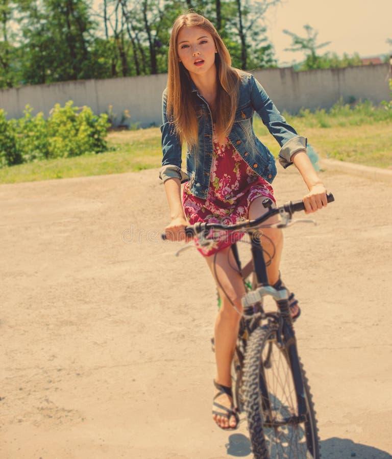 Flicka som rider en cykel arkivbild