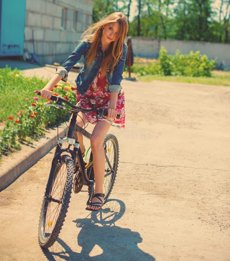 Flicka som rider en cykel royaltyfri bild