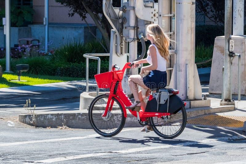 Flicka som rider en elektrisk cykel för hopp arkivbild