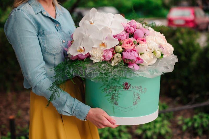 Flicka som rymmer den härliga buketten för blandningvit- och rosa färgblomma i rund ask med locket fotografering för bildbyråer