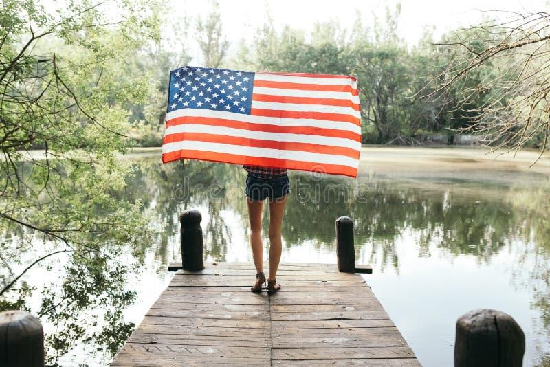 Flicka som rymmer en amerikanska flaggan i natur royaltyfri bild