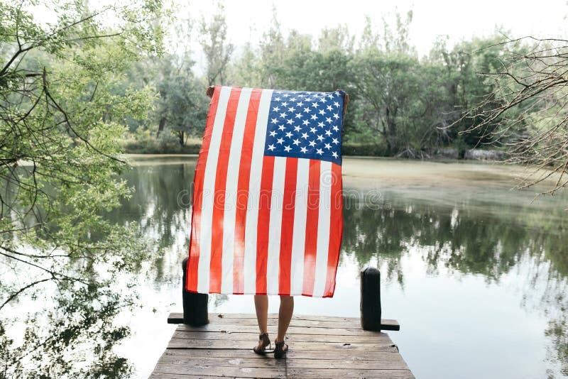 Flicka som rymmer en amerikanska flaggan i natur royaltyfria bilder