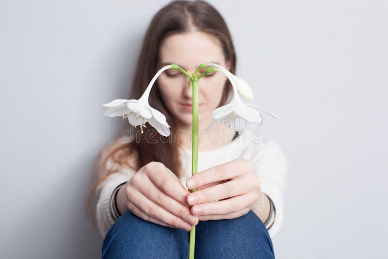 Flicka som rymmer en blomma och ner SAD ser royaltyfri fotografi