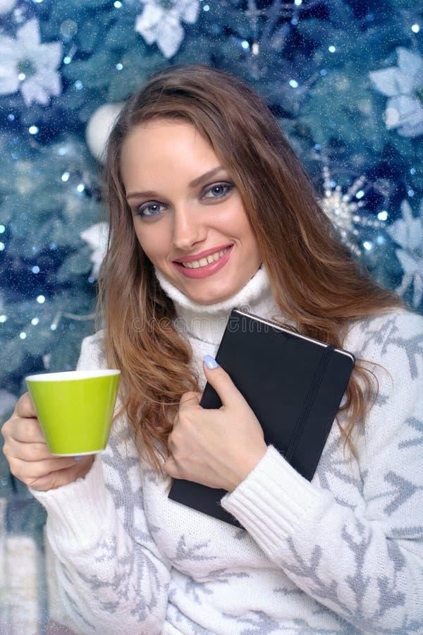 Flicka som rymmer en bok och dricker en varm drink royaltyfria bilder