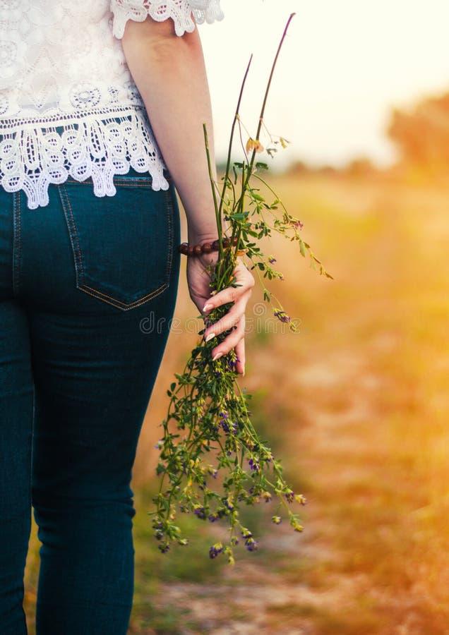 Flicka som rymmer en bukett av en fältblomma i hennes händer i ett fält arkivfoto