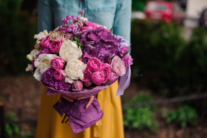 Flicka som rymmer en bukett av purpurfärgade och vita blommor royaltyfri bild