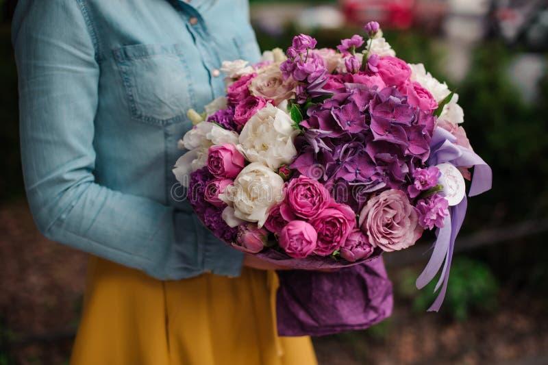 Flicka som rymmer en bukett av purpurfärgade och vita blommor arkivfoton