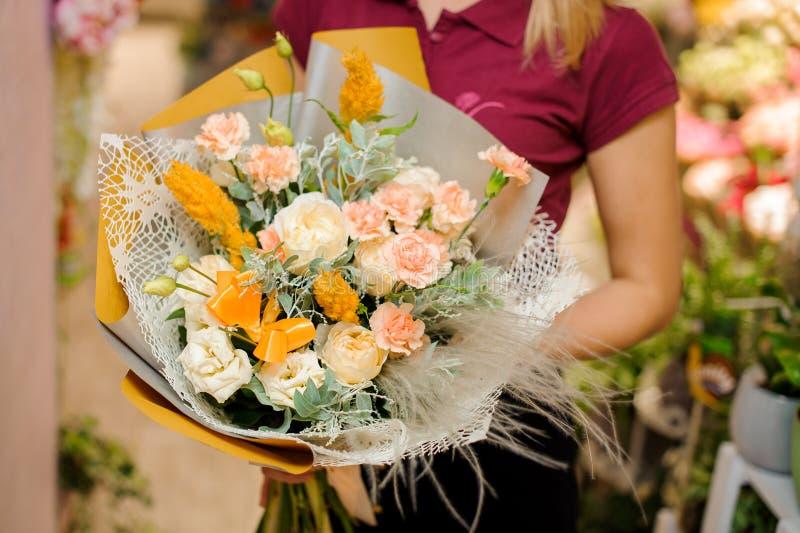 Flicka som rymmer en bukett av rosor, astilbaen och nejlikor royaltyfria foton