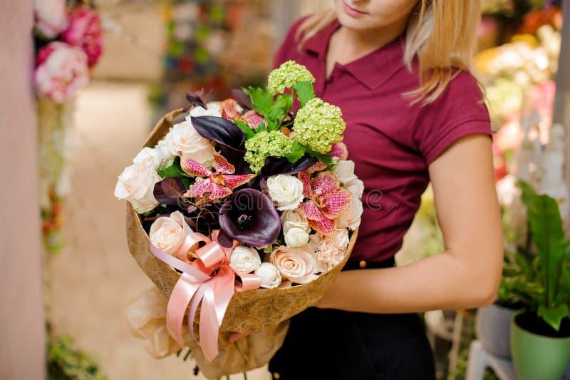 Flicka som rymmer en bukett av rosor, callas, orkidén och vanliga hortensian arkivbild