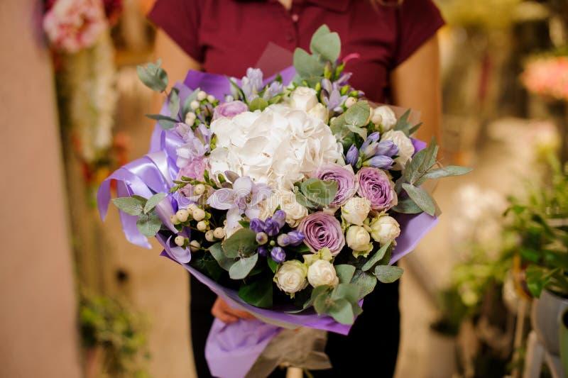 Flicka som rymmer en bukett av rosor, vanlig hortensia, orkidé, eustoma, pioner royaltyfria bilder