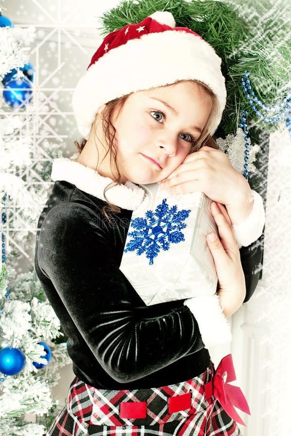 Flicka som rymmer en gåva från Santa Claus arkivfoton