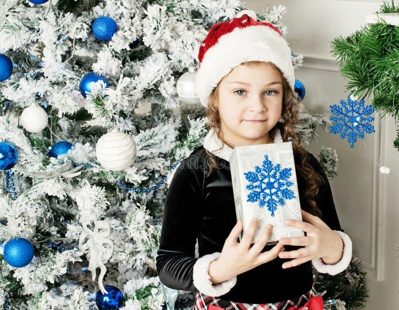 Flicka som rymmer en gåva från Santa Claus fotografering för bildbyråer