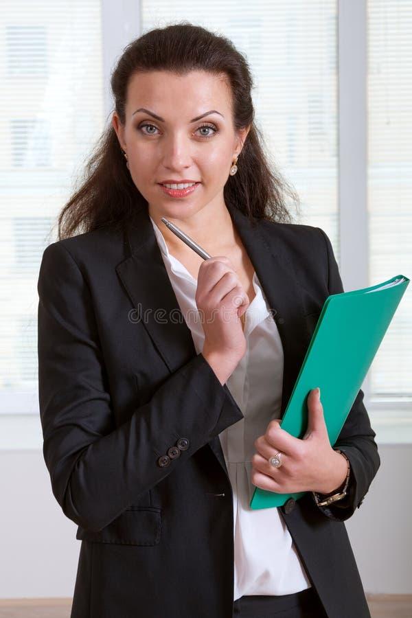 Flicka som rymmer en grön mapp och penna som trycker på hennes haka royaltyfri fotografi