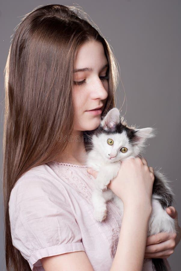 Flicka som rymmer en kattunge arkivbilder