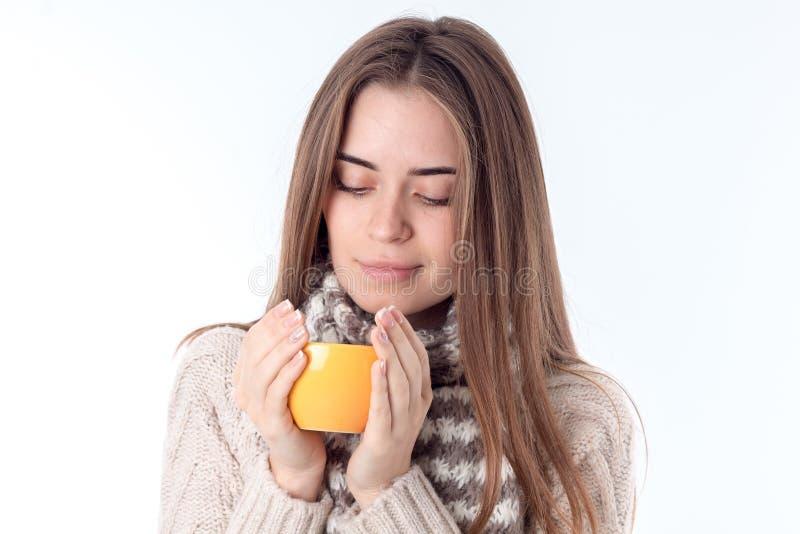 Flicka som rymmer en kopp te och stänger henne ögon som isoleras på vit bakgrund royaltyfria bilder