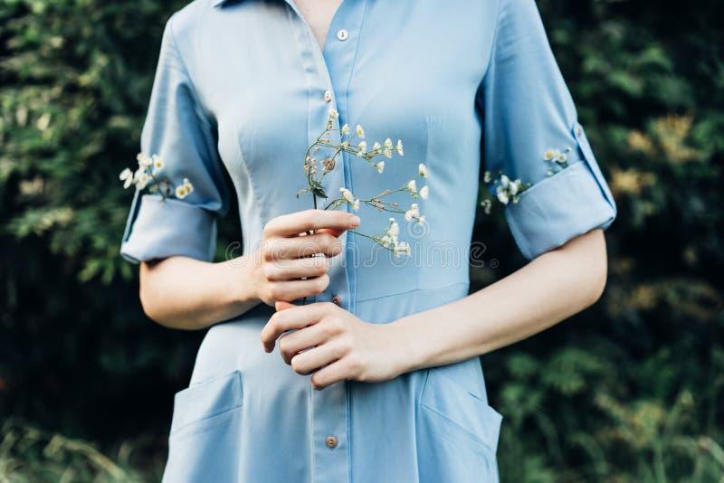 Flicka som rymmer en kvist av lösa blommor royaltyfri fotografi