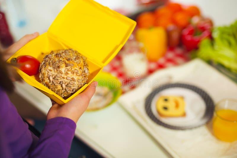 Flicka som rymmer en lunchask i köket arkivfoto