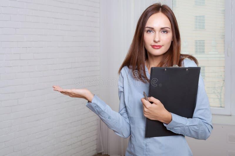 Flicka som rymmer en mapp som uttrycker förvirring royaltyfri bild