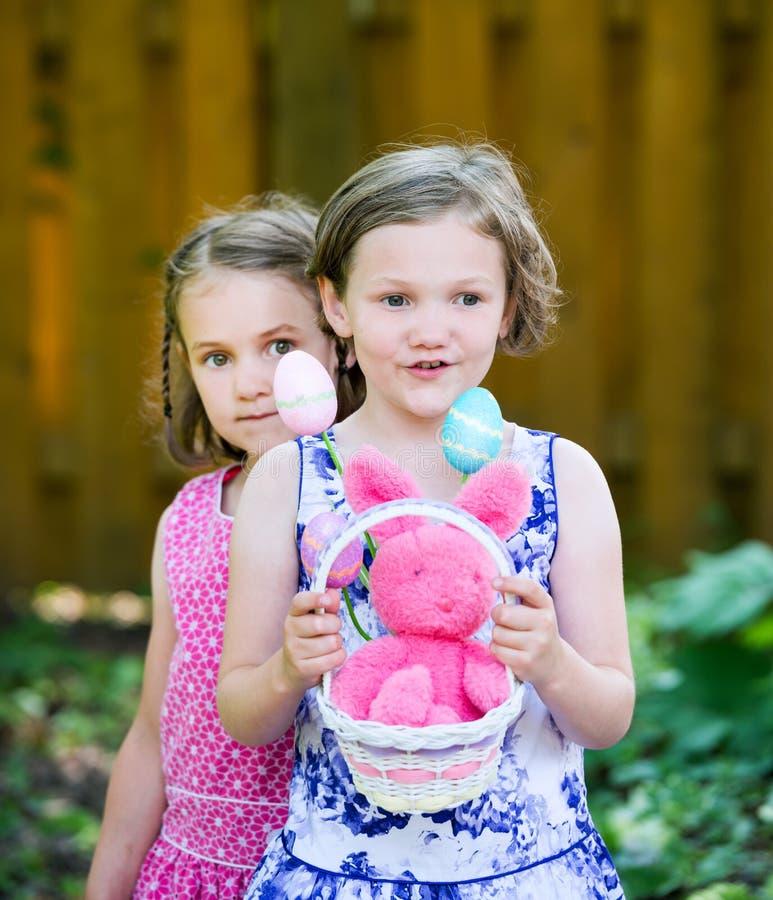 Flicka som rymmer en påskkorg med ägg och kaninen arkivfoto
