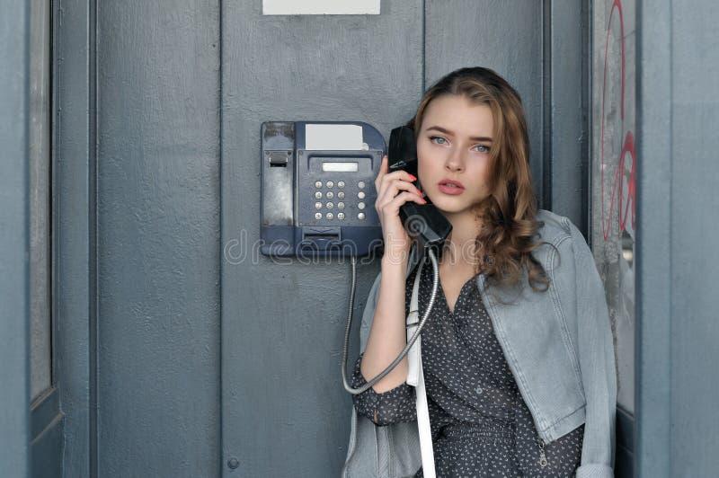 Flicka som rymmer en payphonetelefonlur i hennes hand arkivfoton