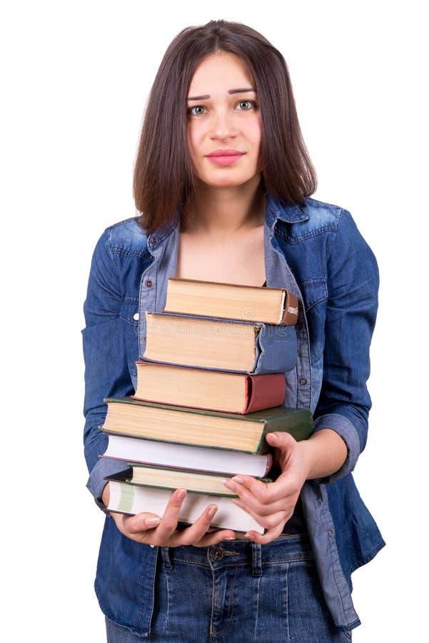 Flicka som rymmer en stor bunt av böcker arkivbild
